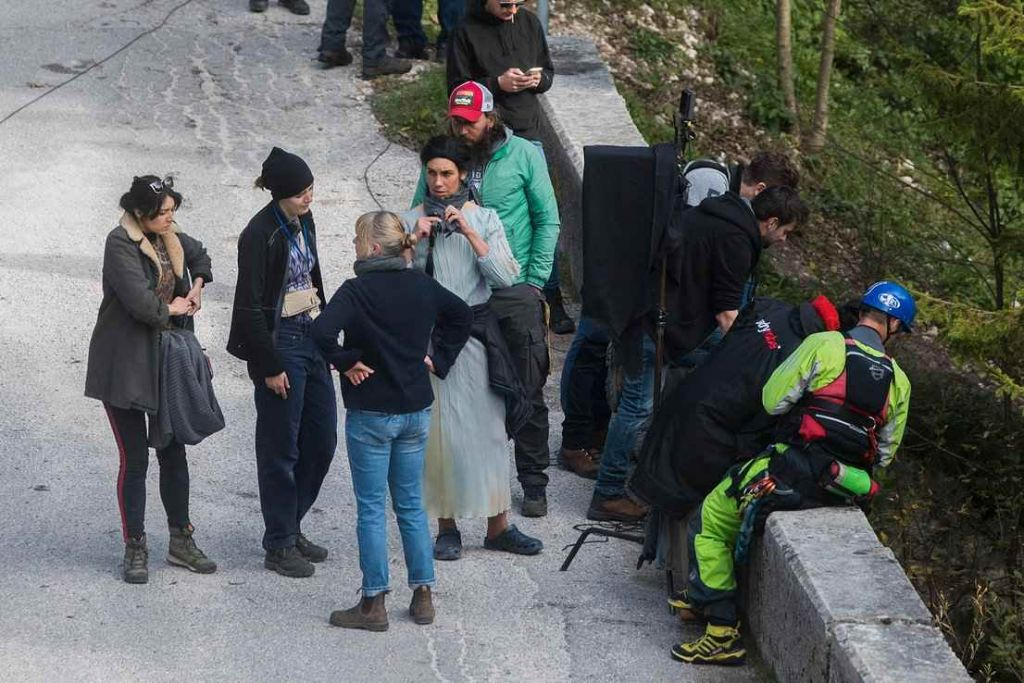 A group of film crew on a bridge, including a stuntwoman in a long dress and braid