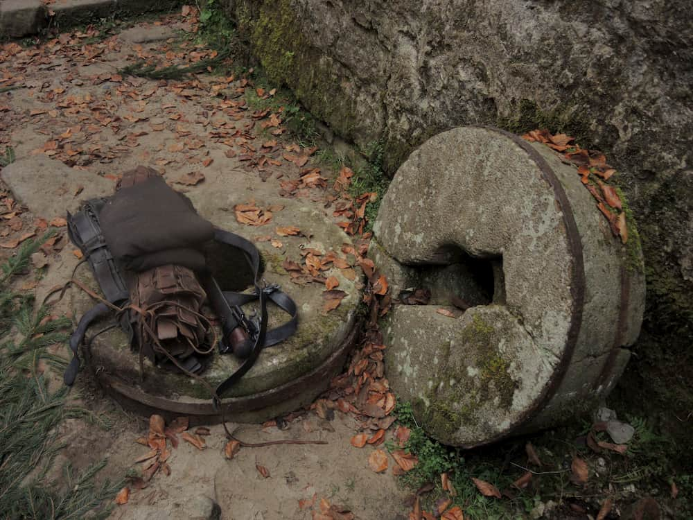 The photo shows blankets, some rolled up leather, and a handle. The gear is laying on the ground in some ruins.
