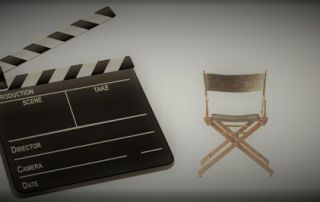 Image of a film slate in the foreground and an empty audition chair in the background