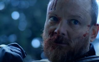 a bald man with blood on his face, seemingly in combat