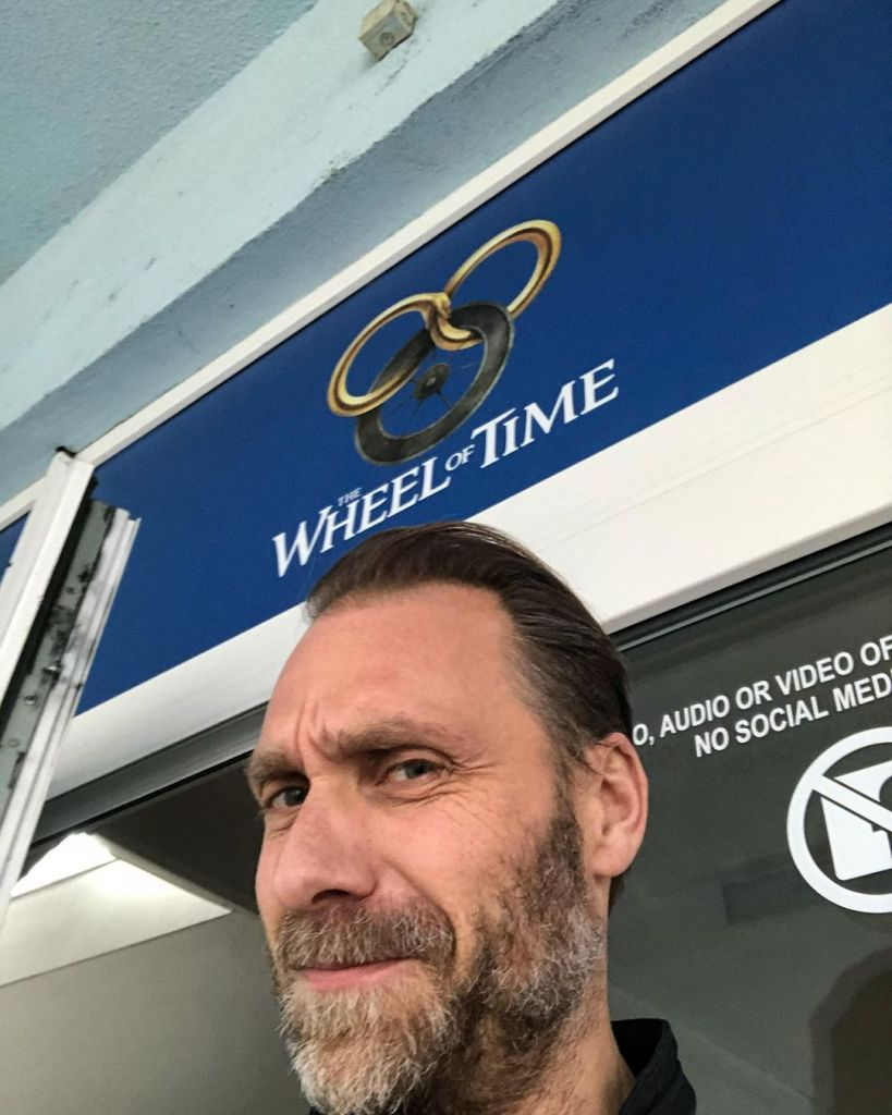 A selfie of Alexandre Willaume in front of a blue banner with the old Wheel of Time Logo.