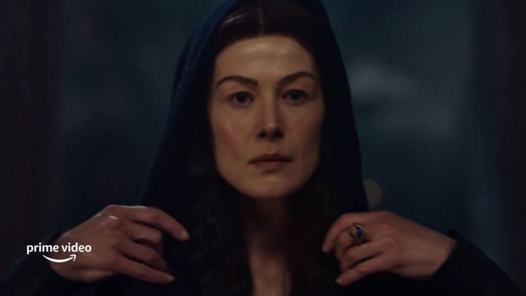 Moiraine reaches for the hood of her cloak to lower it